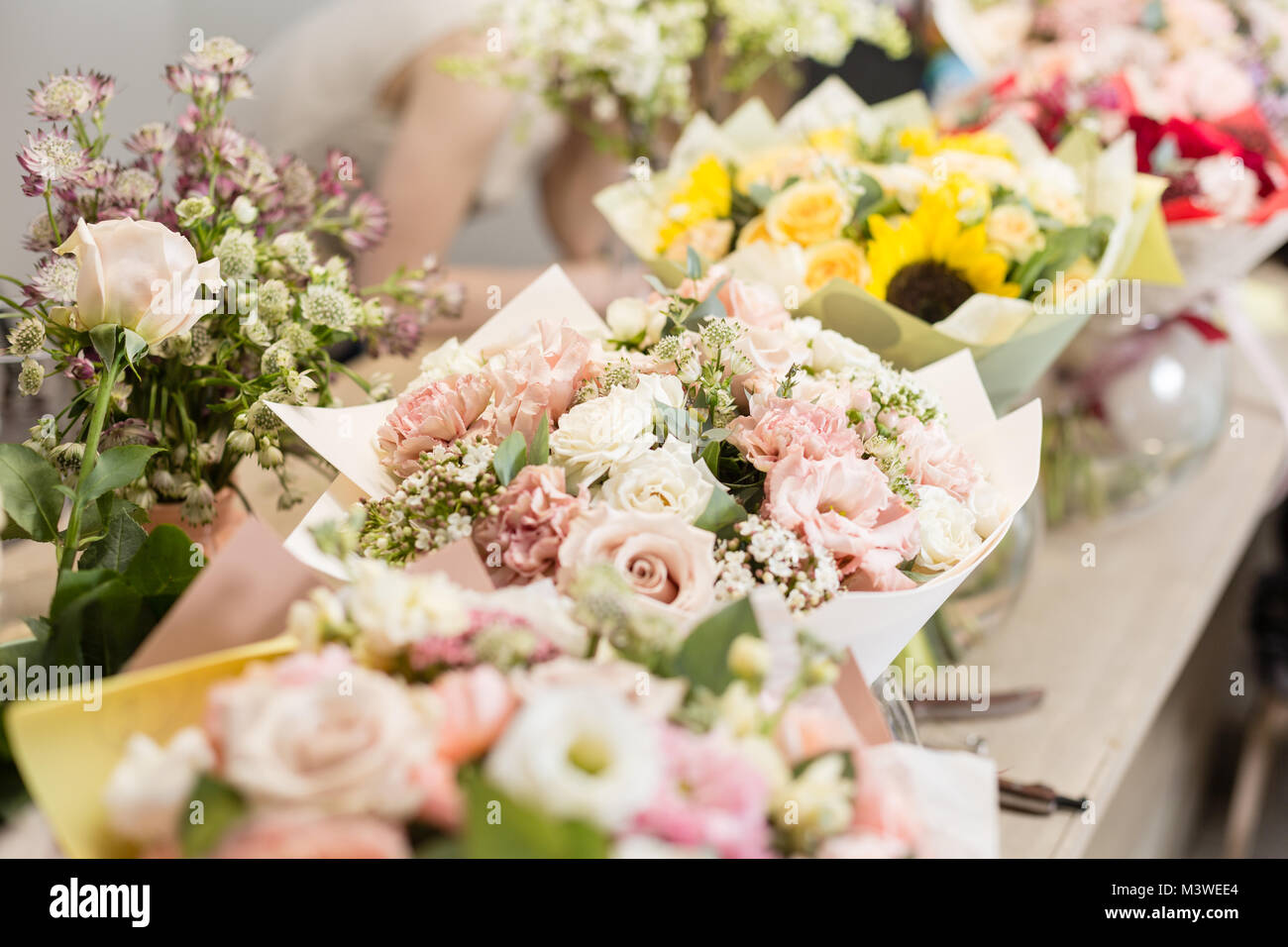 Bouquets on table, florist business. Different varieties fresh spring flowers. Delivery service. Flower shop concept. - Stock Image