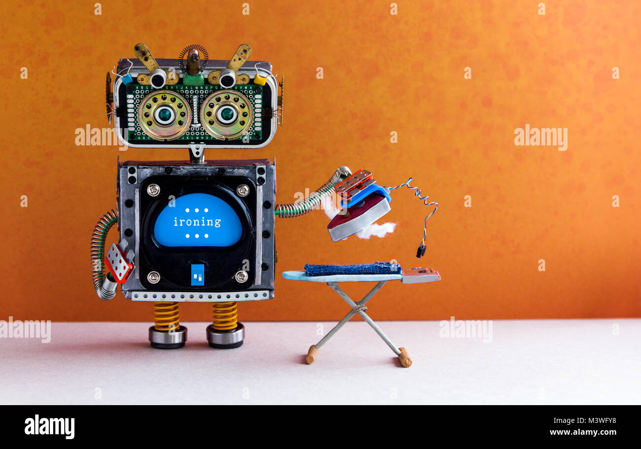 Robotic housework assistant ironing blue jeans with iron on the board. Orange wall gray floor room interior. Creative - Stock Image