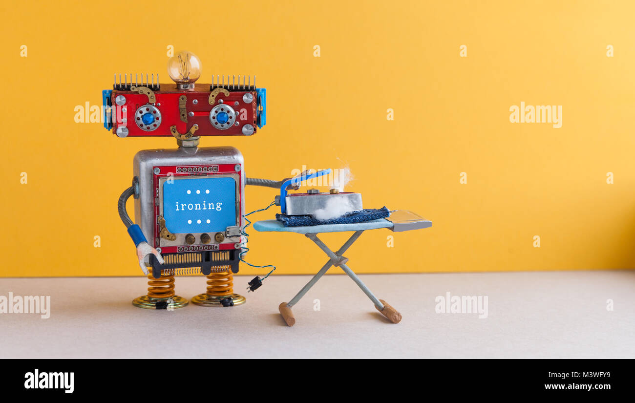 Ironing blue jeans with board. Robot housework helper with iron, yellow wall gray floor room interior. Creative - Stock Image
