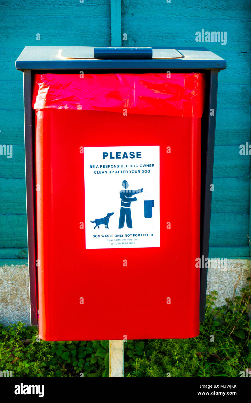 """Bright red bin situated outside for dog waste, with a label reading: """"Please be a responsible dog owner. Clean up - Stock Image"""