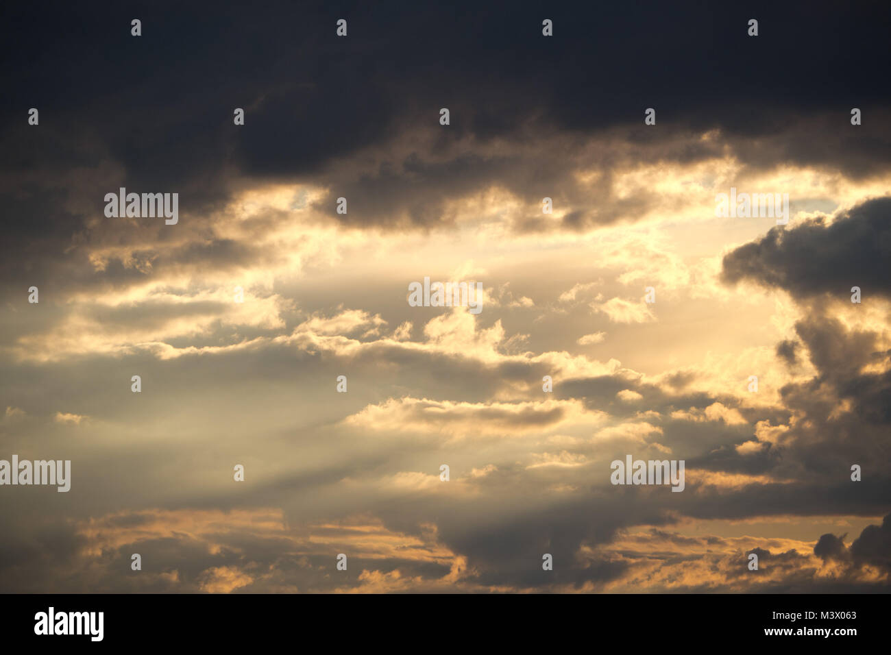 Sunset cloudy sky with sunlight gleams - Stock Image