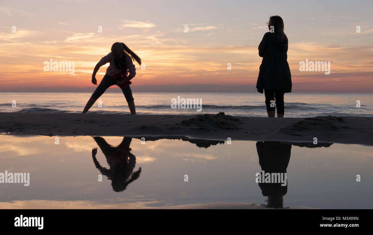 Amazing sunset with sun reflections on the sea guestig two silhouettes reflecting in still sea water on the beach - Stock Image