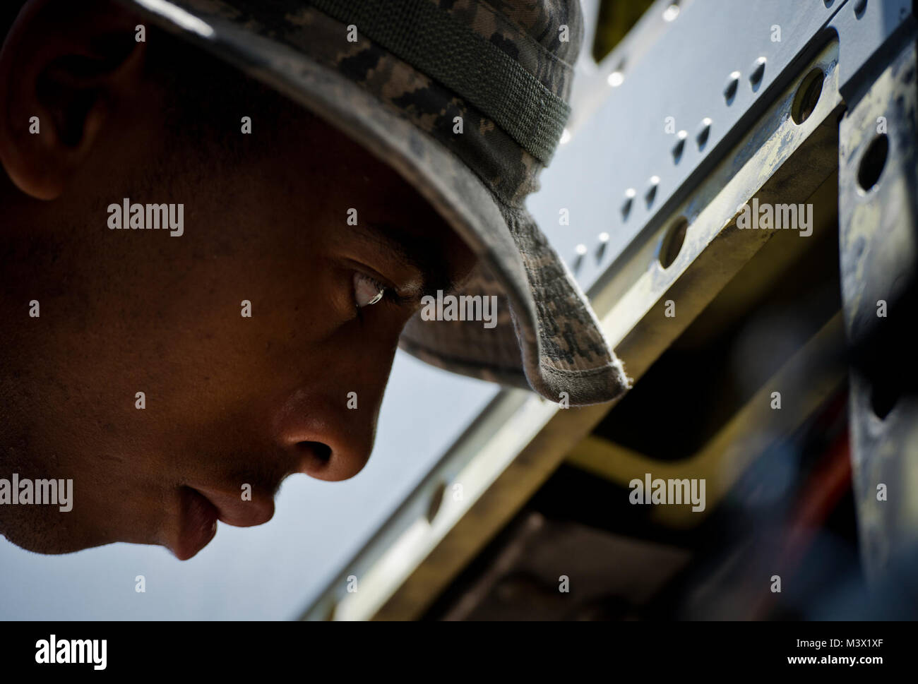 Senior Airman Aaron Augustus looks inside one of the four Rolls-Royce AE 2100D3 turboprop engines on a WC-130 Hercules - Stock Image