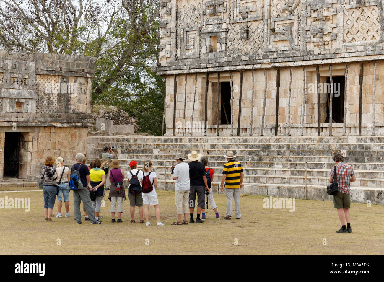 Group of tourists in the Nunnery Quadrangle at the Mayan ruins of Uxmal, Yucatan, Mexico - Stock Image