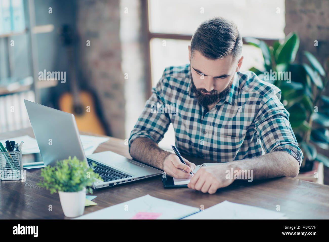 Attentive smart clever intelligent male student wearing checkered shirt is doing homework at home in front of modern - Stock Image