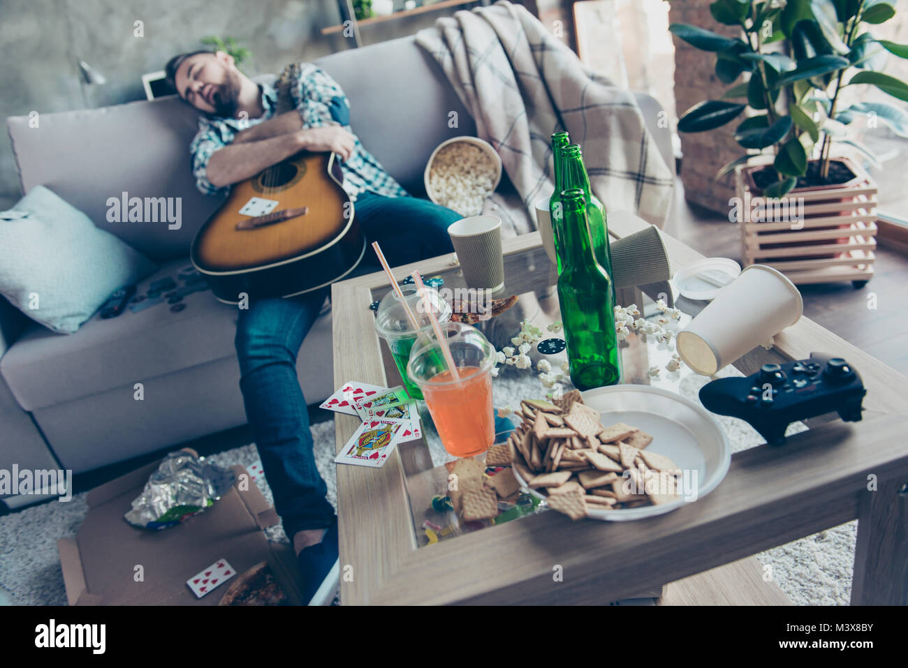 After party morning, bachelorette party. Drunk hipster embracing an acoustic guitar is sleeping on a sofa in messy - Stock Image