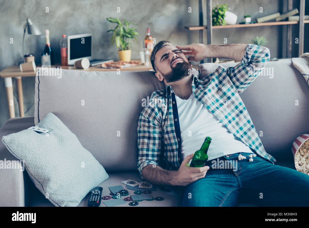 Handsome, stylish man suffering from headache after night party in the morning, holding bottle of beer in hand, - Stock Image