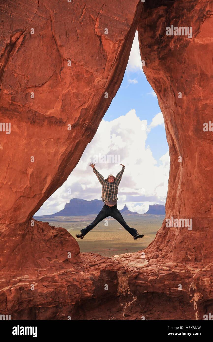 Female hiker jumping inside Teardrop Arch in Southern Utah - Stock Image