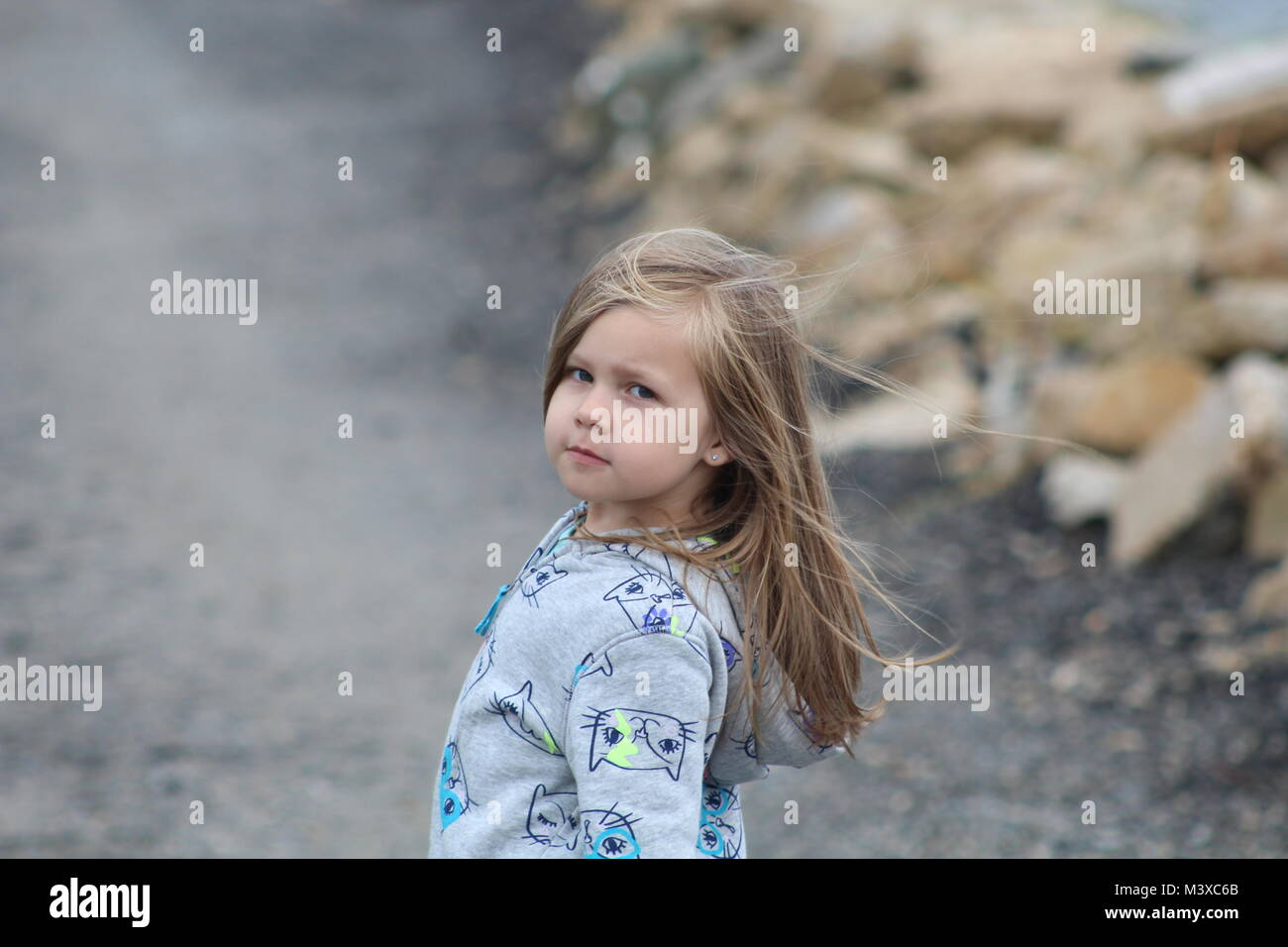 5 year old granddaughter on a rainy day on the path to the beach in Virginia - Stock Image