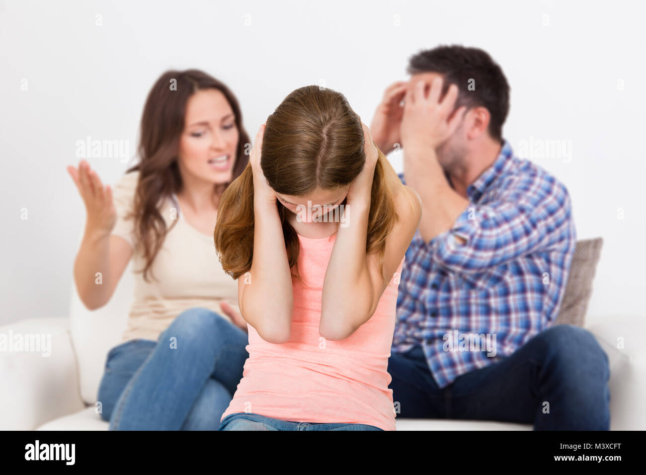 Parent Sitting On Sofa Quarreling Loudly Behind Girl Covering Her Ears - Stock Image