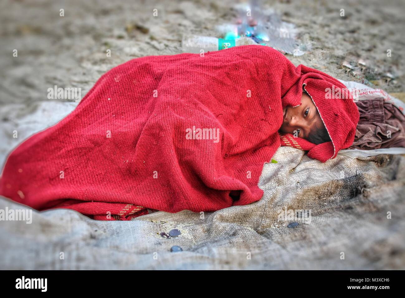 Sick Teenage Boy Lie Down At Road For Beg - Stock Image