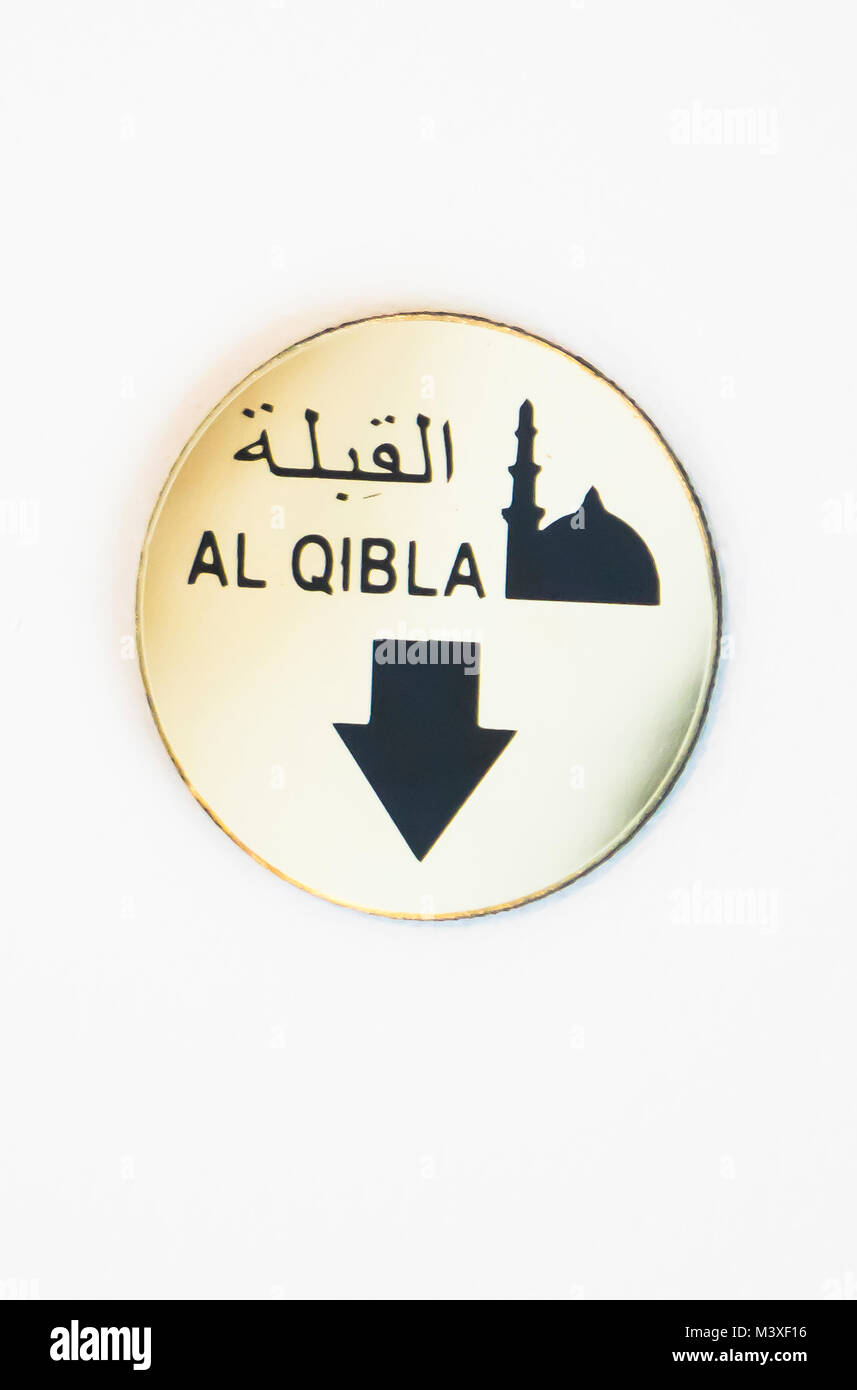 Al Qibla sign in hotel ceiling, showing the direction of Mecca, thus the way Moslems should face during prayers - Stock Image