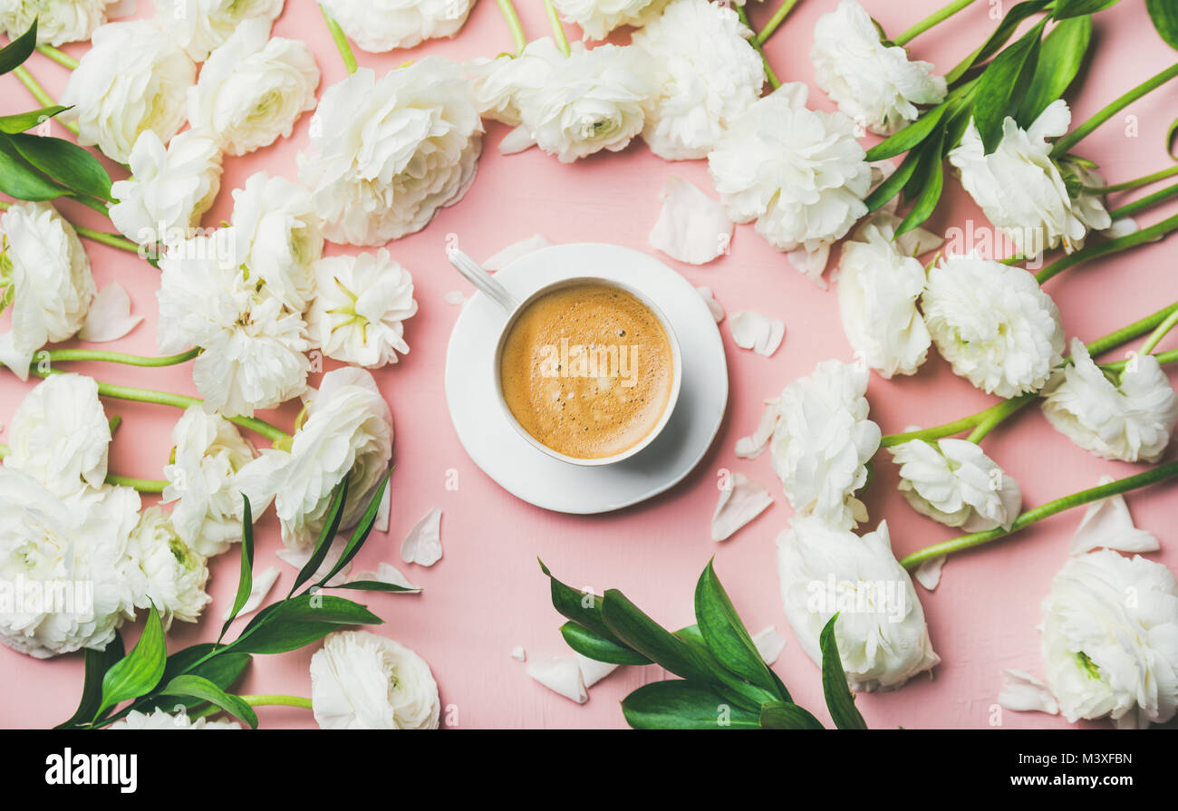 Flat-lay of cup of coffee surrounded with white ranunculus flowers - Stock Image