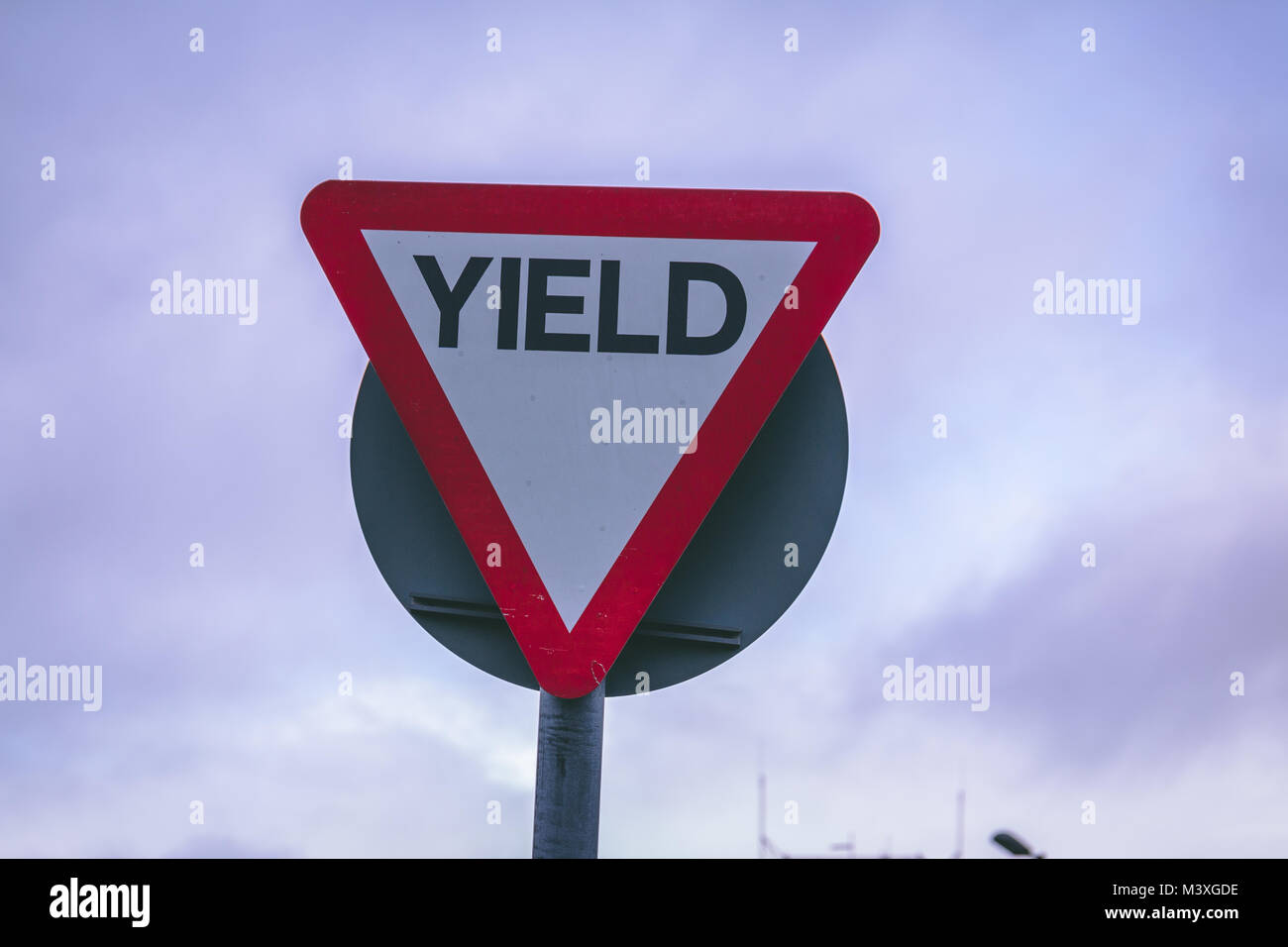 Close up of a yield road sign on a cloudy day - Stock Image