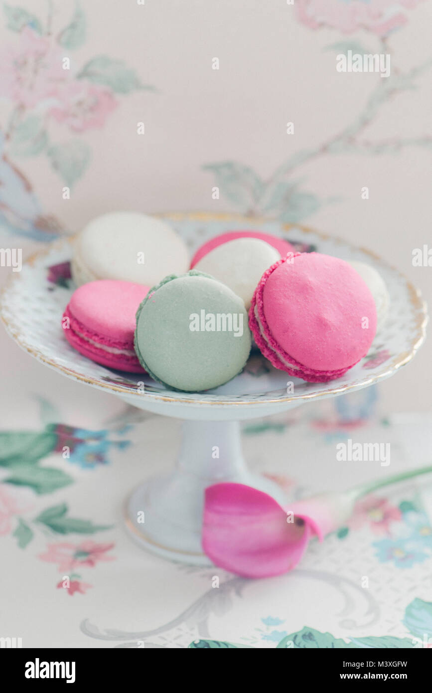 Macaroons on a pedestal plate with a floral background - Stock Image