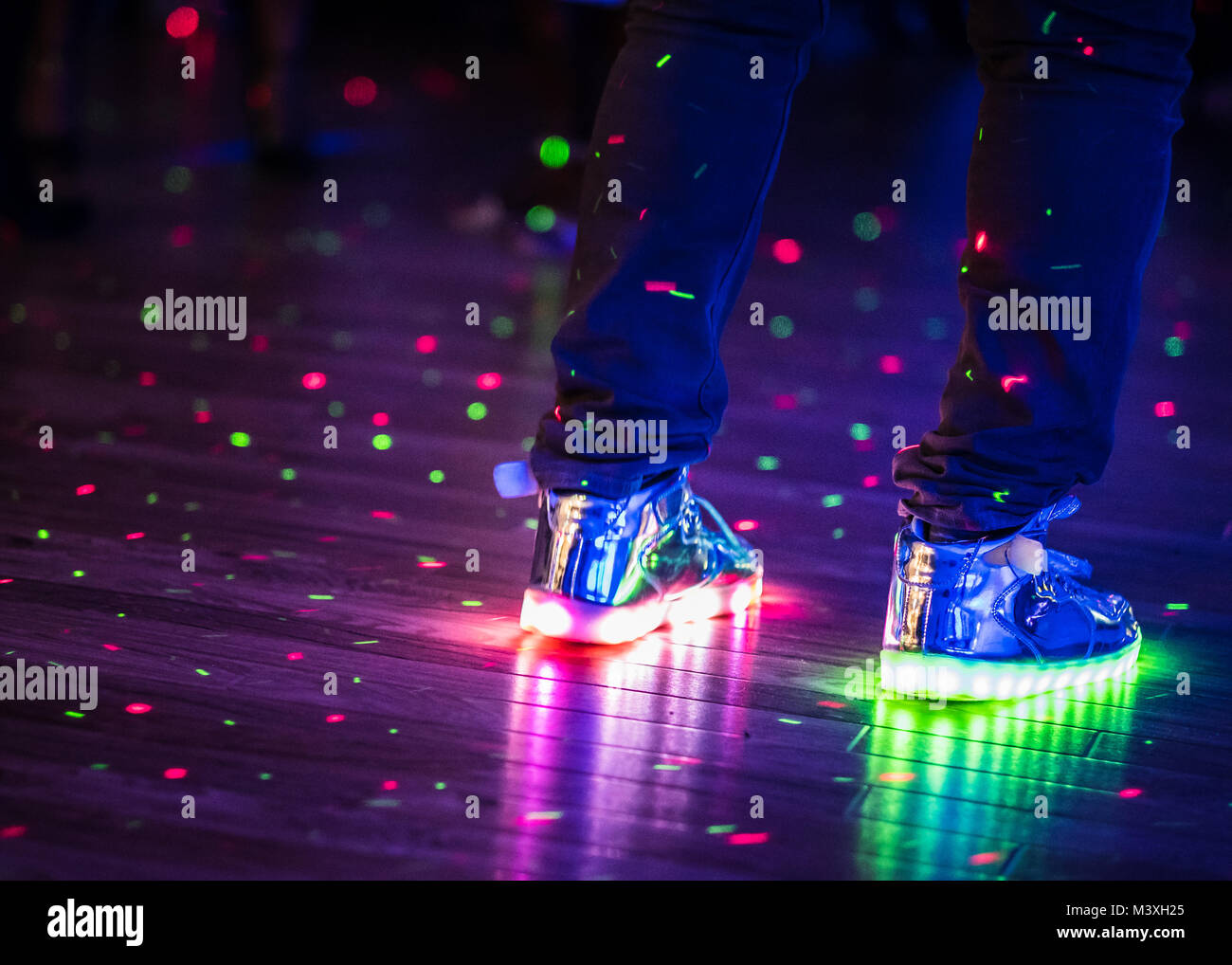 Flashing multi-coloured changing shoes in a night club. - Stock Image
