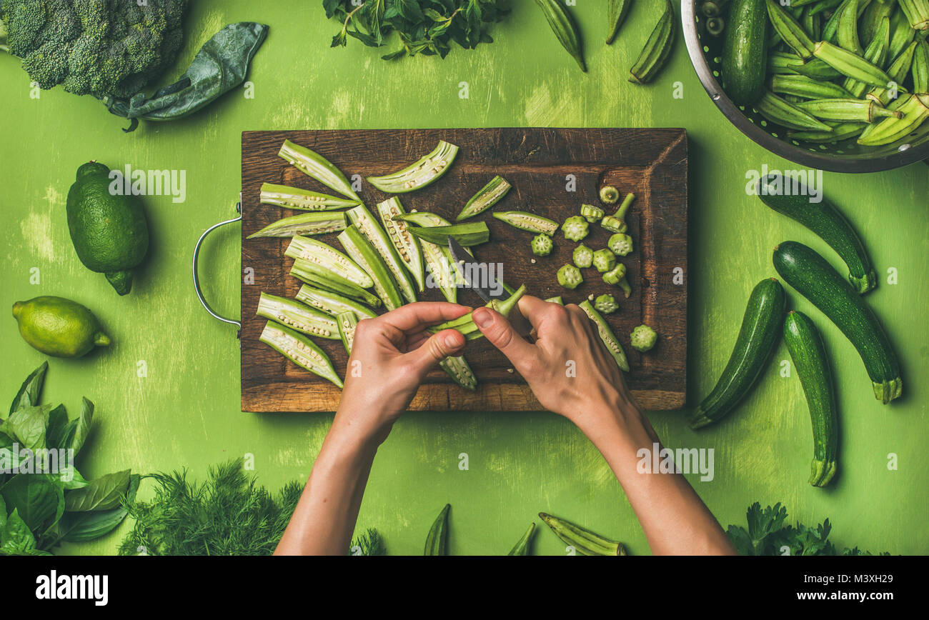 Flat-lay of healthy green vegan cooking ingredients over green background - Stock Image