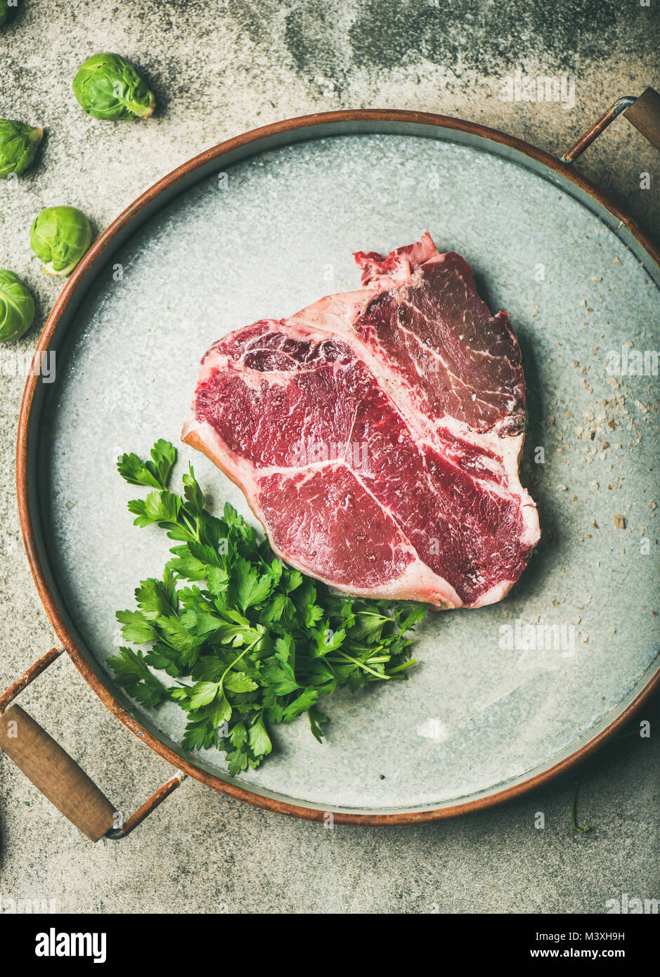 Flat-lay of raw uncooked dry-aged t-bone prime beef steak - Stock Image