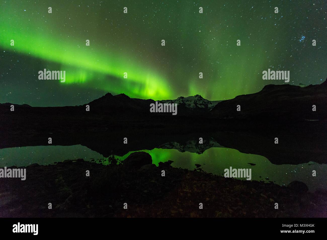 Green aurora light behind Lake mountain in iceland europe at national park skaftafell - Stock Image