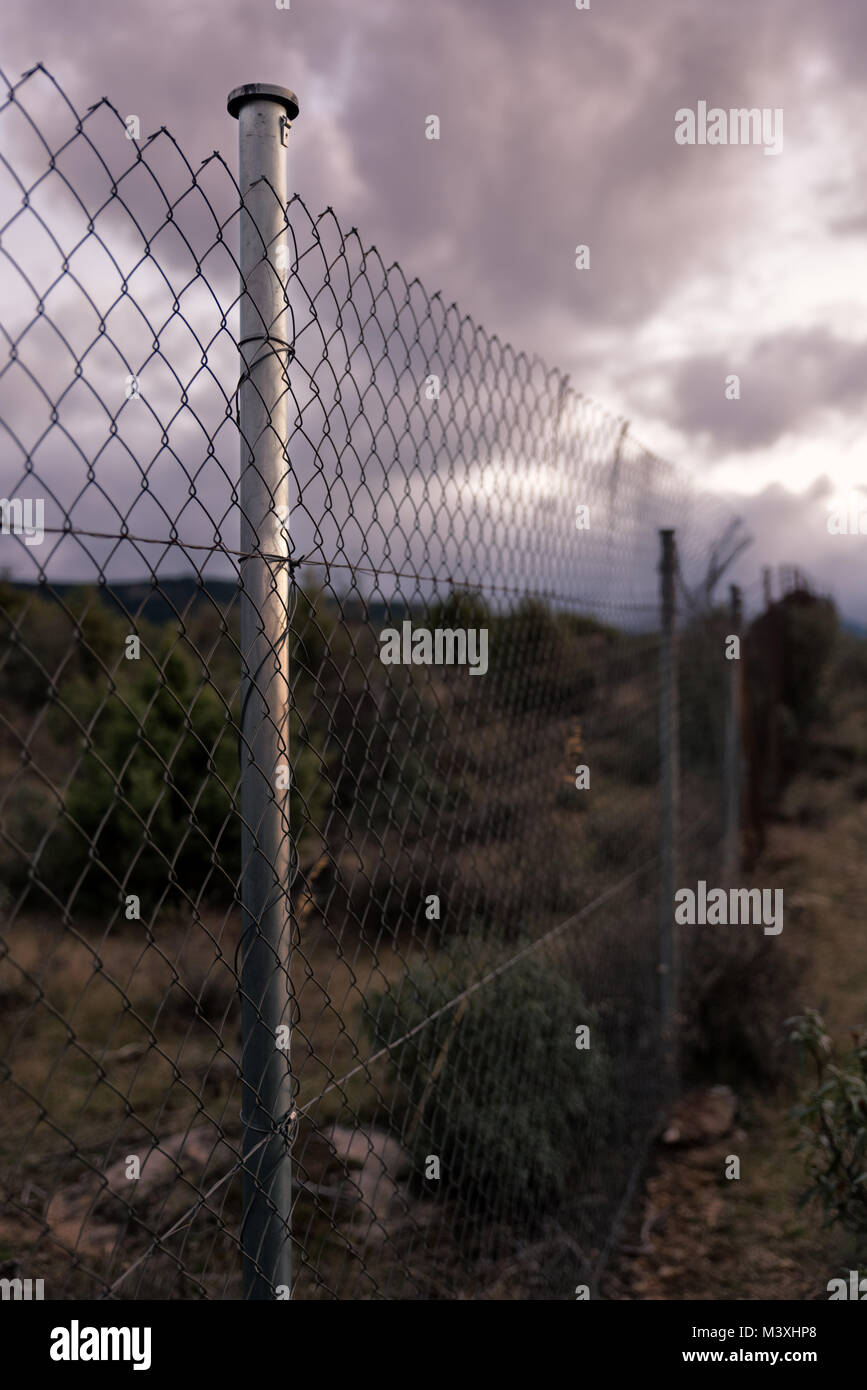 Apocalyptic scene of barbed wire fence and cloudy sky - Stock Image