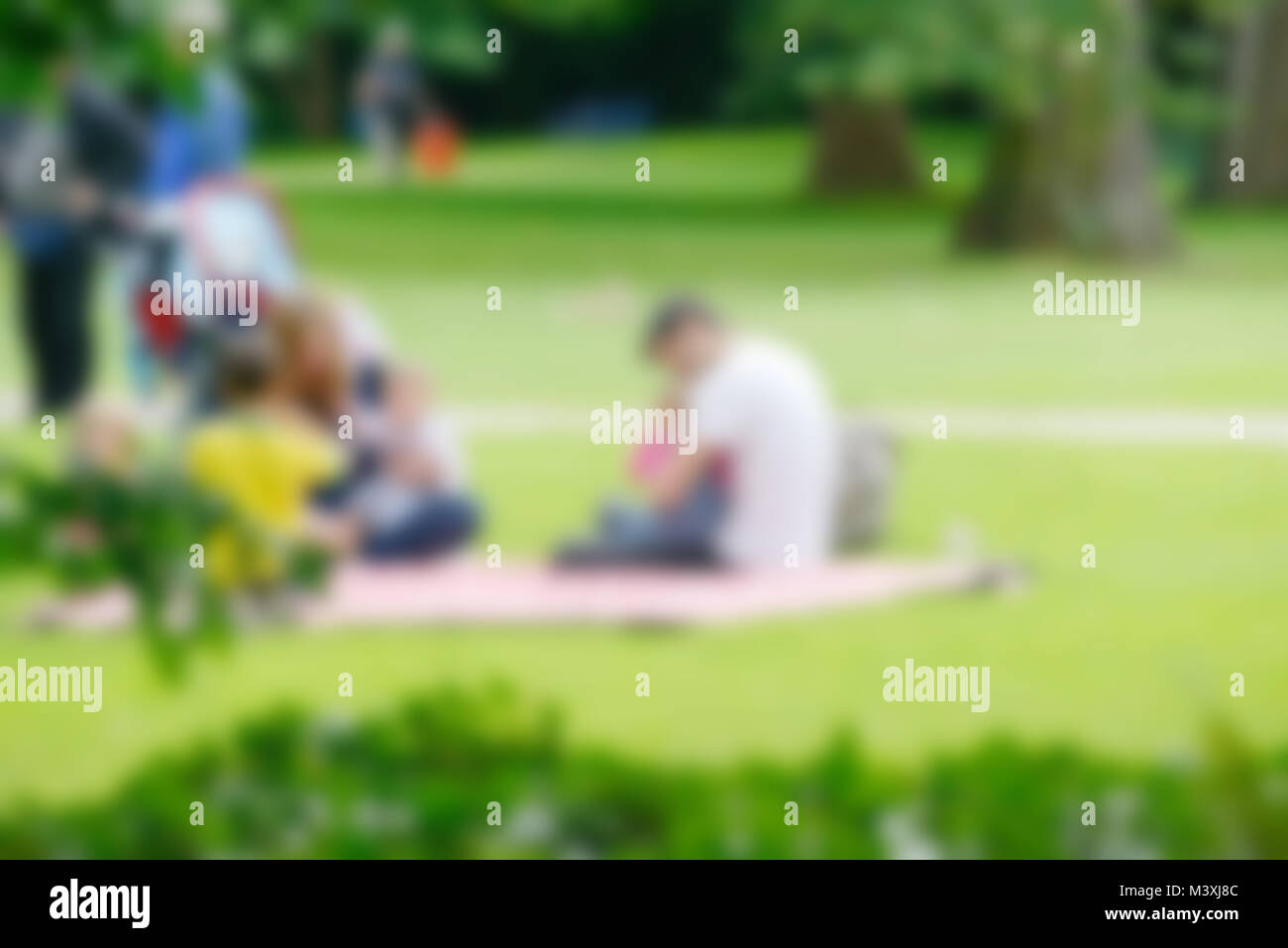 Blurred image of young family with children in summer park. Stock Photo
