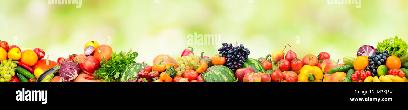 Panoramic collection fresh fruits and vegetables on green background. Free space for text. Stock Photo