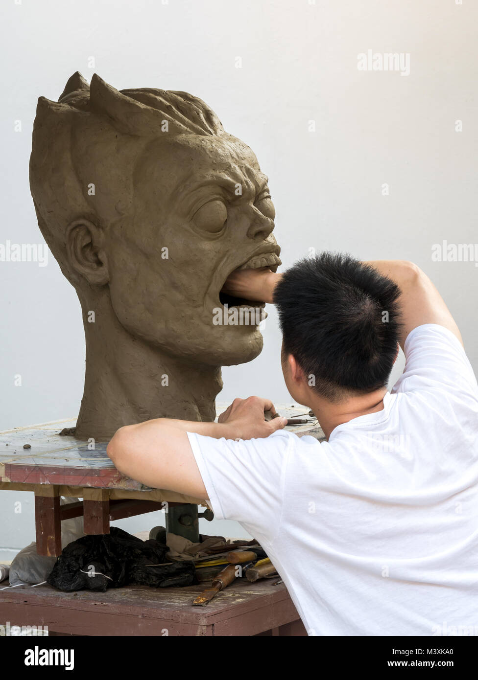 Sculptor working on his clay sculpture, a big portrait,with white background - Stock Image