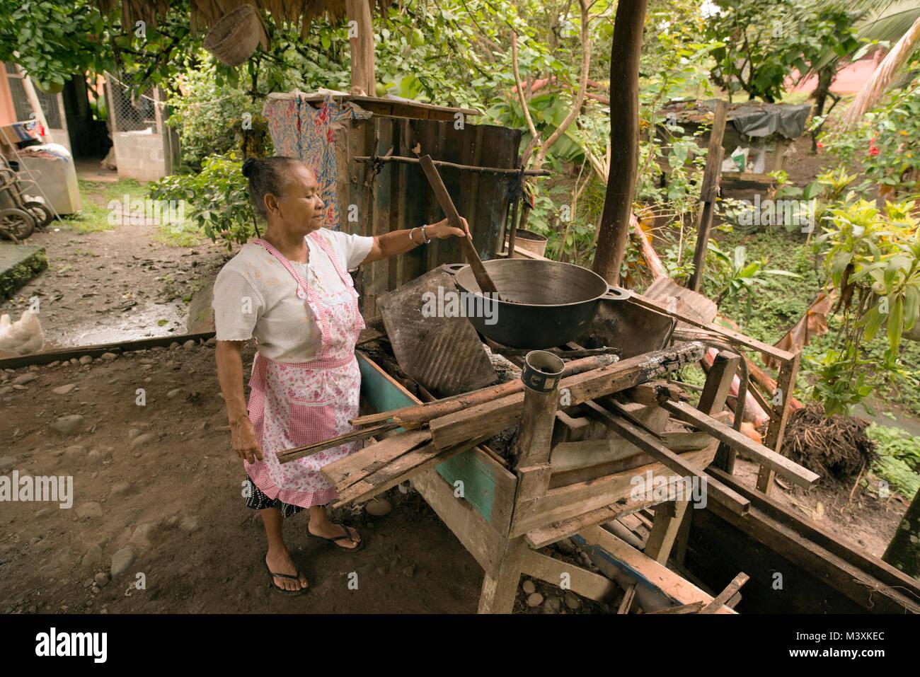 An elderly, indigenous Bribri lady roasts cocoa beans. - Stock Image