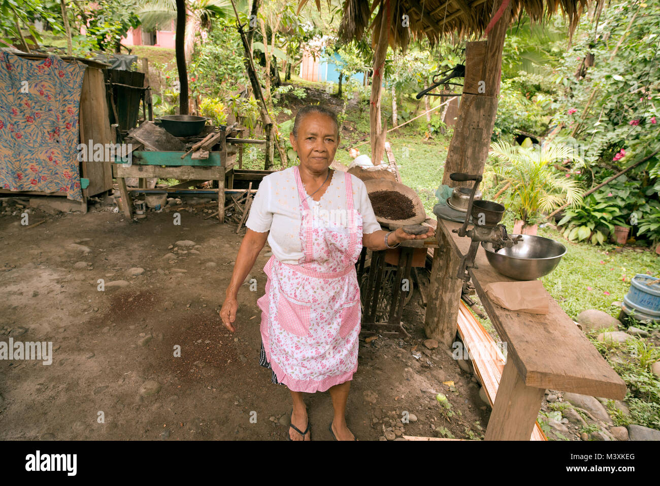 An elderly, indigenous Bribri lady makes chocolate paste from cocoa beans. - Stock Image