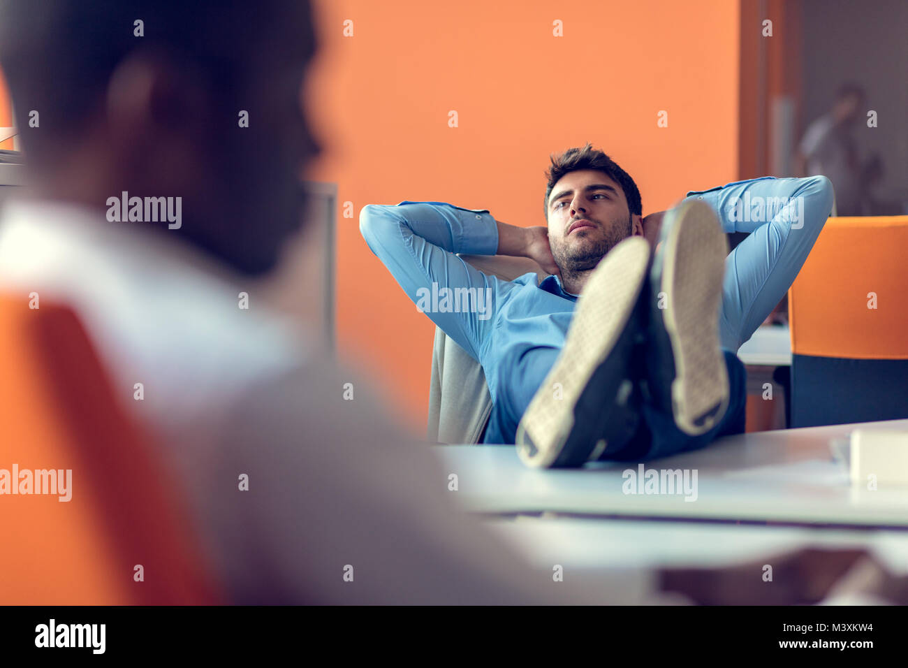 Taking time for a minute break. Cheerful young man holding hands behind head - Stock Image