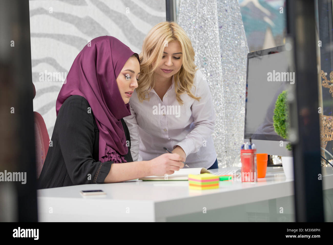 European woman and asian muslim woman working together on same project - Stock Image