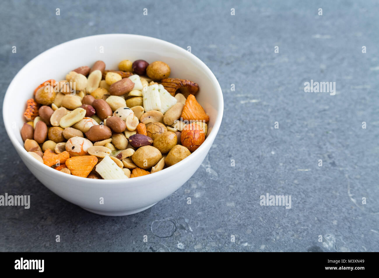 Nuts and seeds in white bowl on dark grunge texture background - Stock Image