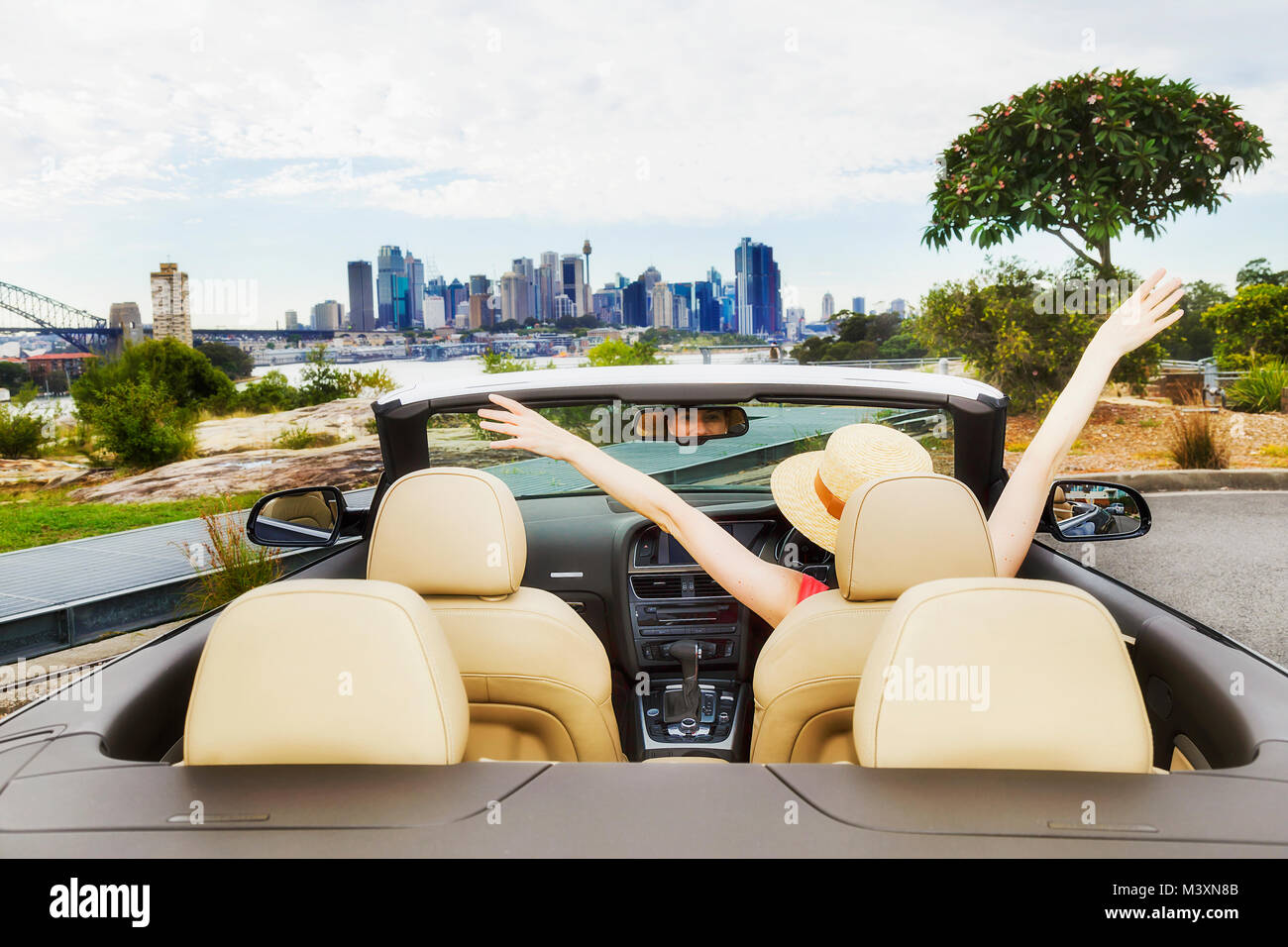 Open space in modern luxury passenger sports car with soft top down and happy lady driver enjoying wealthy and healthy - Stock Image
