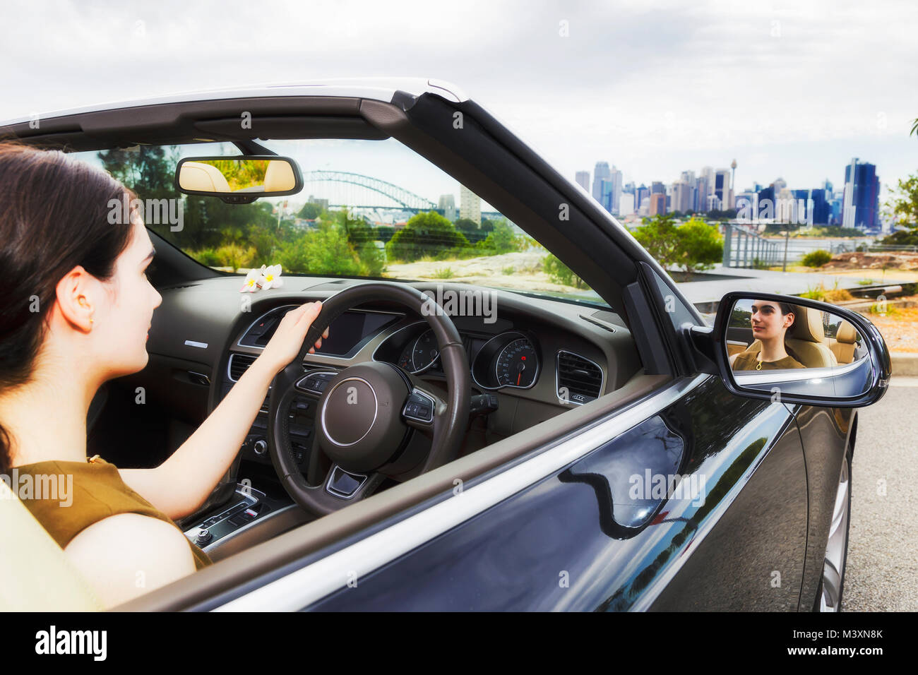 Young learning lady driver of teenage millenial age steering a luxury convertible car with soft top down in Sydney - Stock Image
