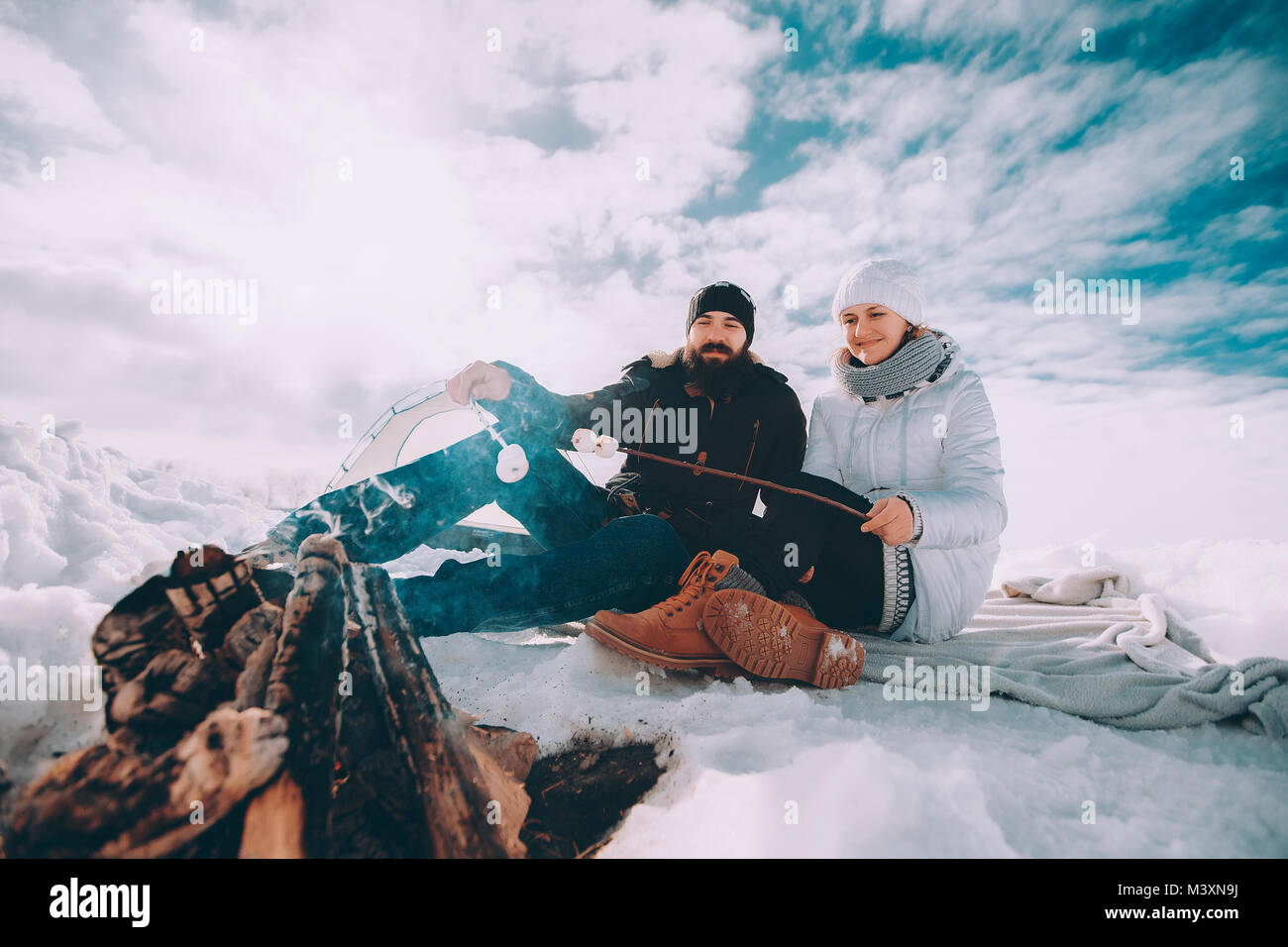 lovers roast marshmallow over a campfire - Stock Image