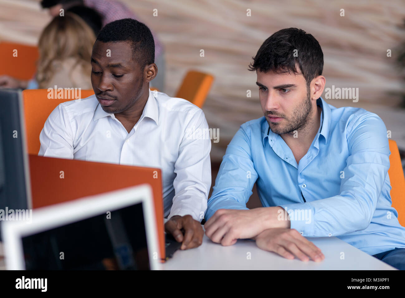 Two smart businessman using smartphone and laptop workig in office. - Stock Image