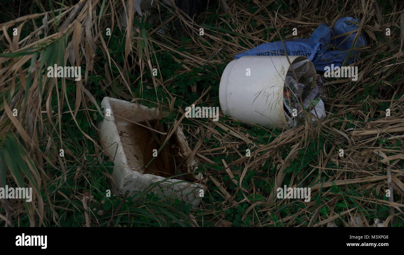 A bunch on trash surrounded by weed. - Stock Image