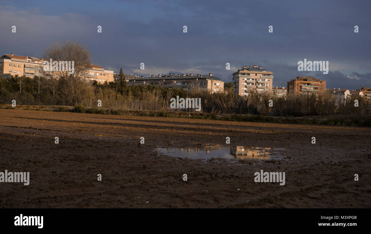 A puddle reflecting an apartment inside a filed on a winter's afternoon sunset. - Stock Image