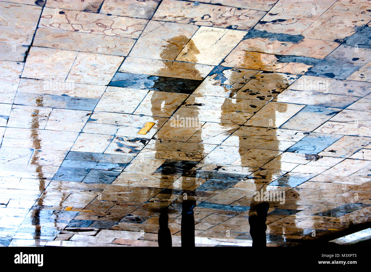 Blurry rainy day, a person walking under umbrella reflection silhouettes on wet city square  in high contrast Stock Photo