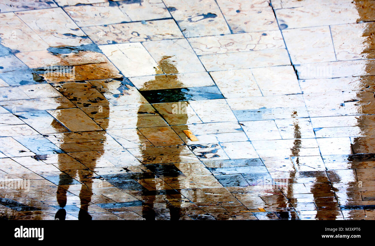 Blurry rainy day, people walking under umbrella reflection silhouettes on wet city square  in high contrast Stock Photo