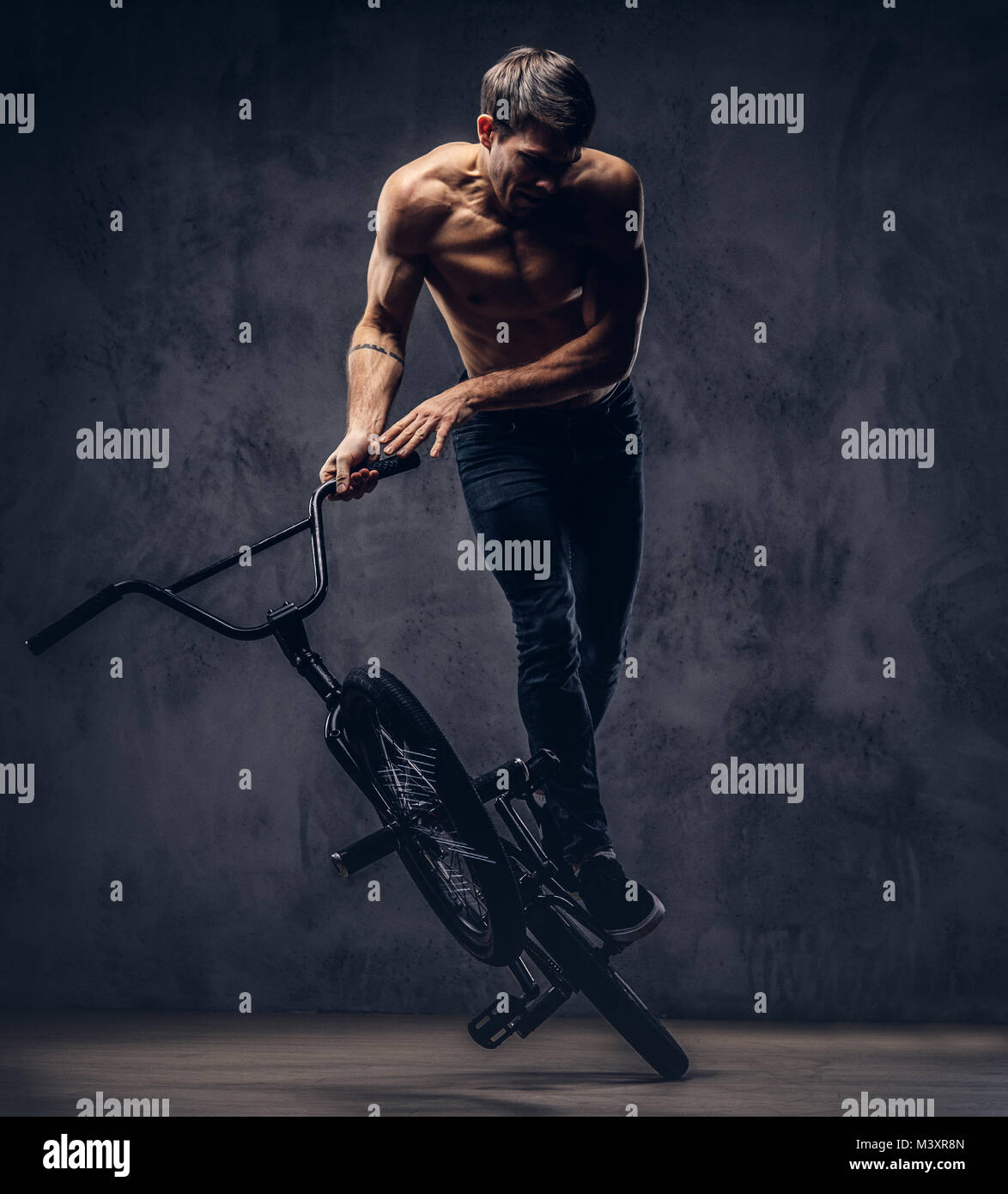 A handsome man with BMX in a studio. - Stock Image
