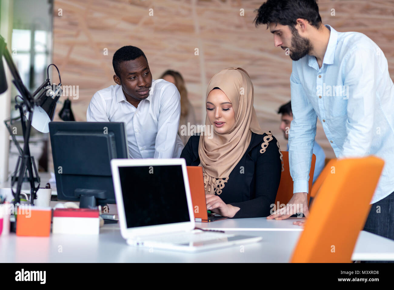 startup business team on meeting in modern bright office interior brainstorming, working on laptop and tablet computer - Stock Image