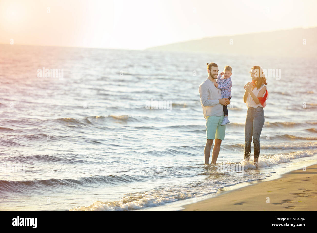 portrait of happy family and baby enjoying sunset in the summer leisure - Stock Image