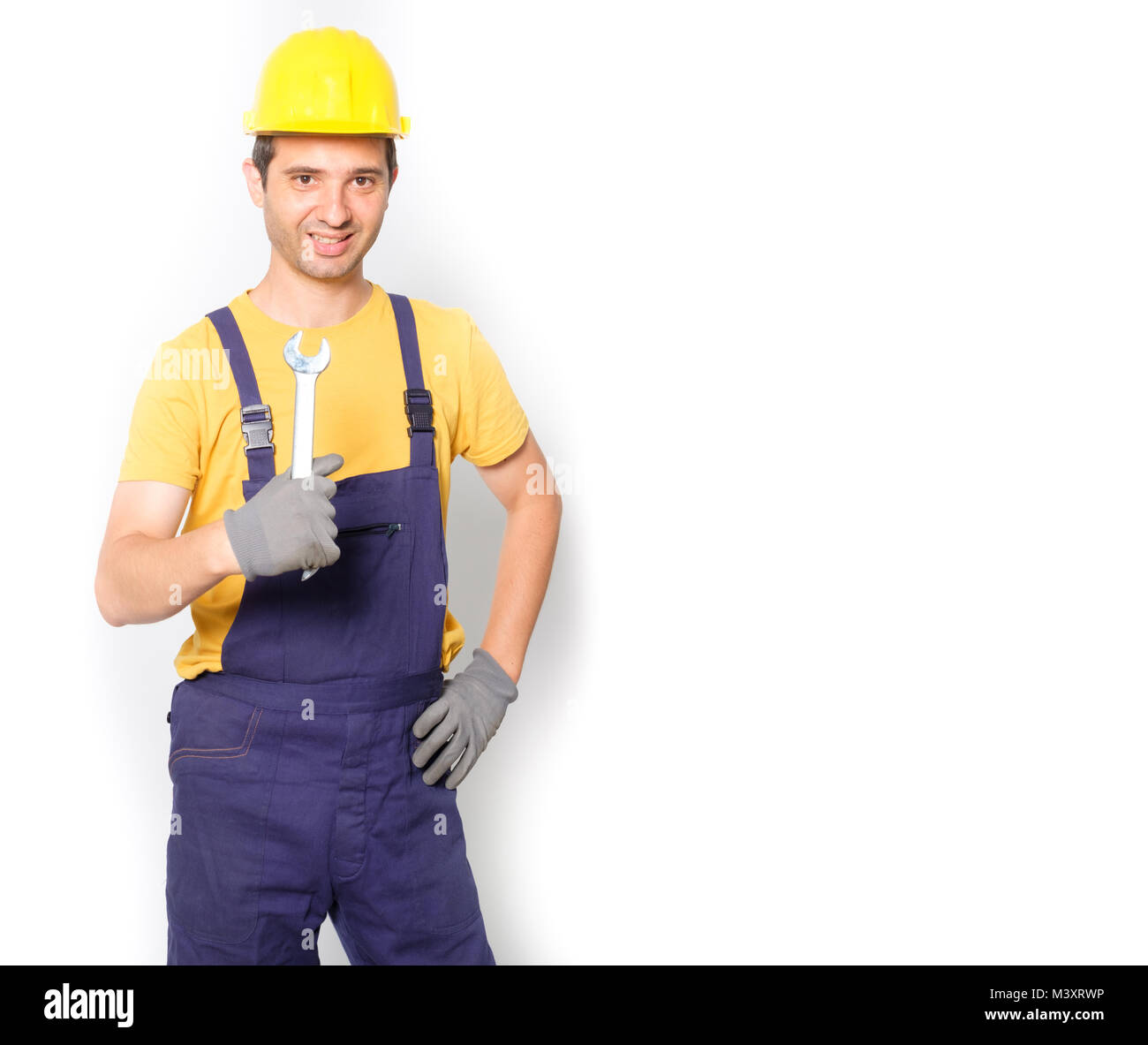 Worker mechanic holding a wrench  isolated on white background - Stock Image