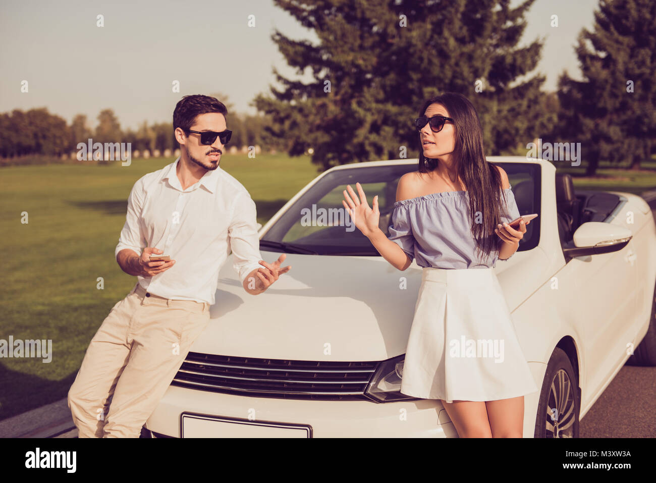 Angry partners on journey trip, escape drive ride, guy in formal wear sist on a hood, lady leaning it. Driver and - Stock Image