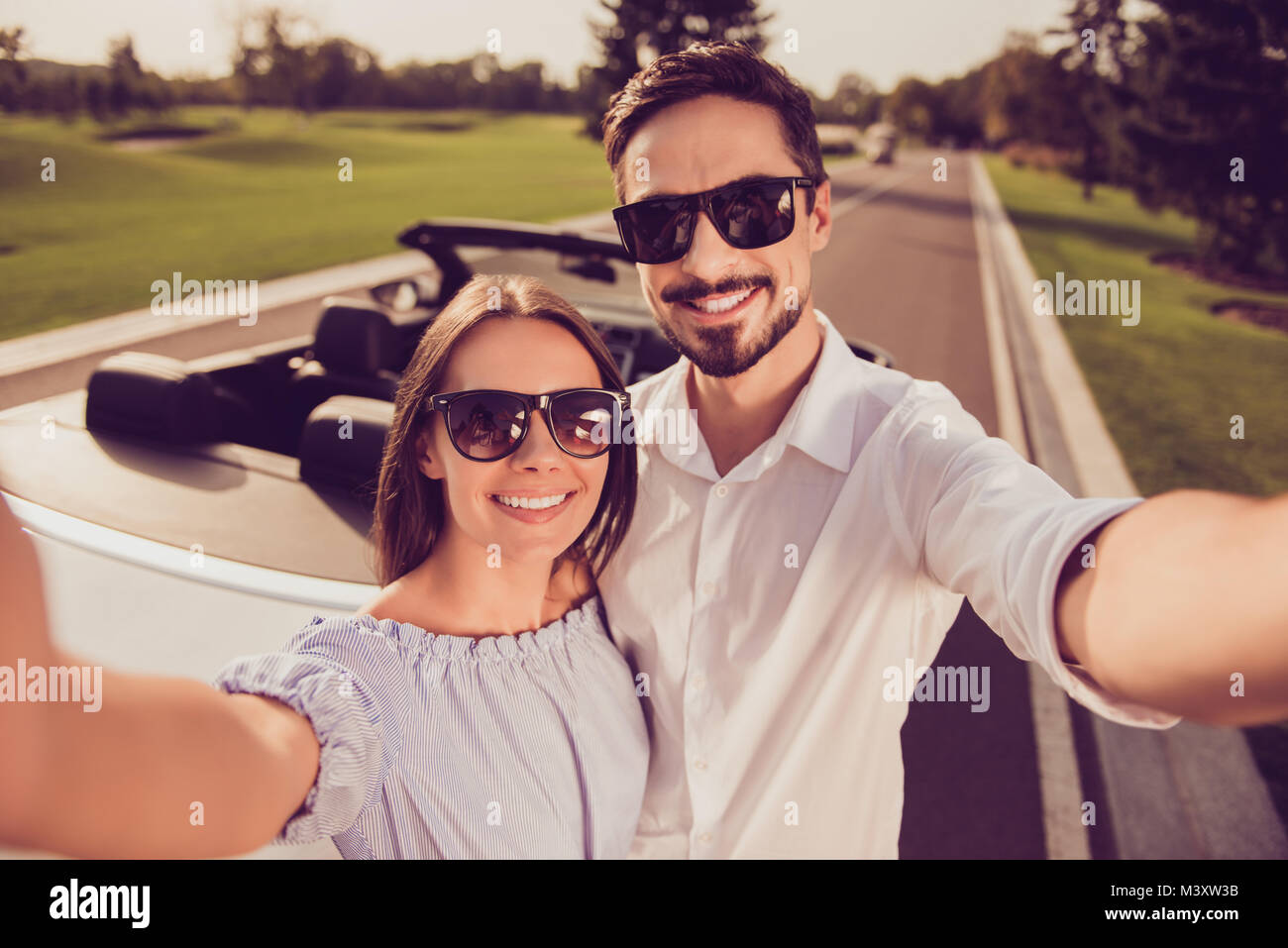 Cute gorgeous sweet partners with beaming grins taking photo on camera, luxury vehicle transportation behind, they - Stock Image
