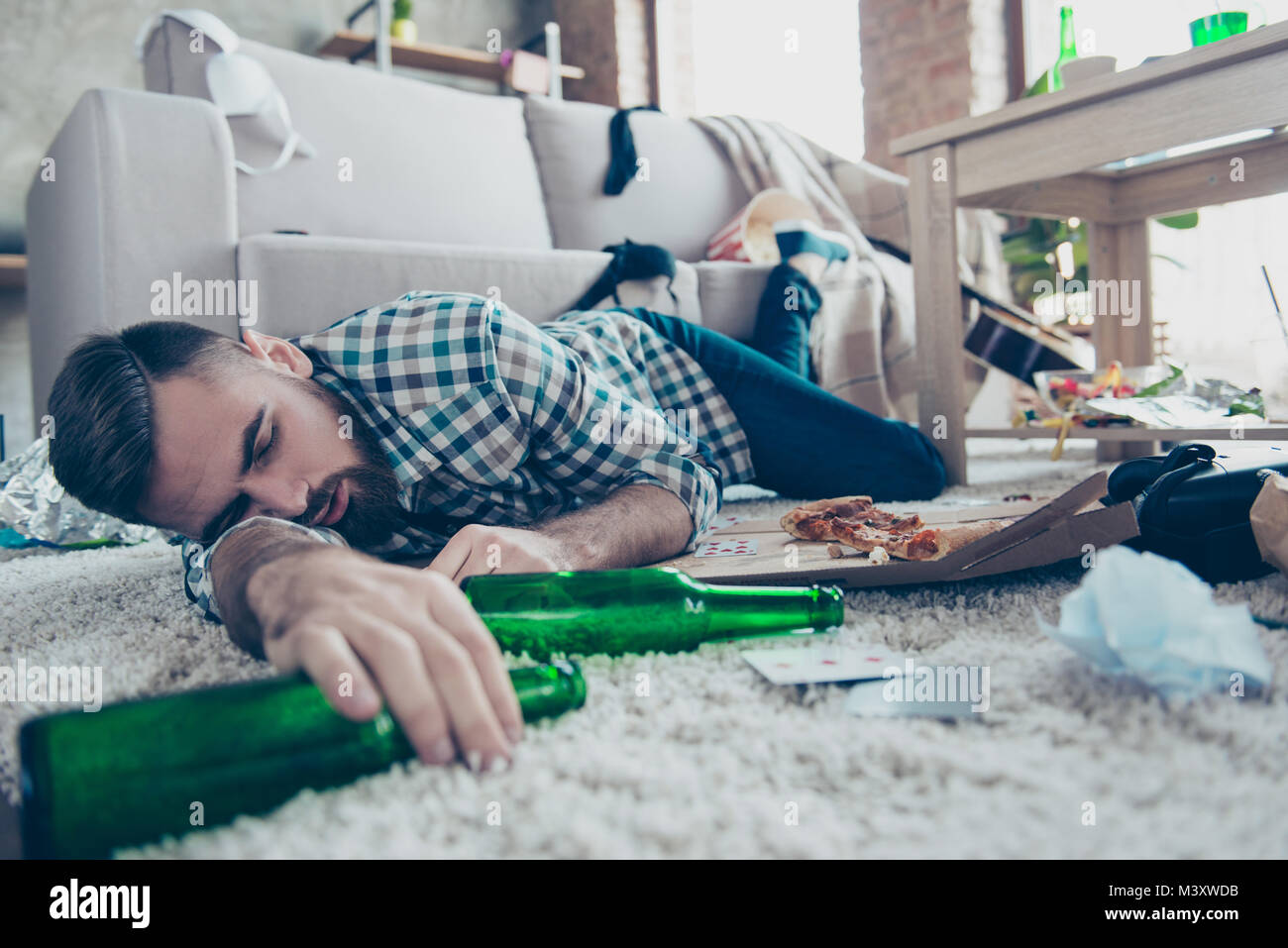 Sick drunk dreamy bearded guy clothed in checkered shirt and denim jeans is sleeping on the floor with an empty - Stock Image