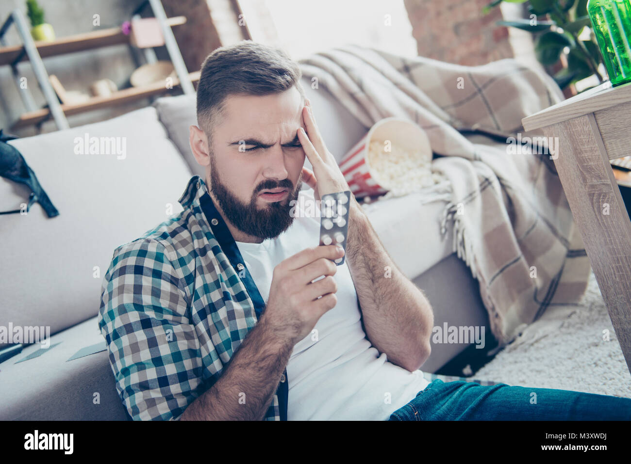 Close up portrait of sick ill feeling unwell sad troubled upset bearded guy touching his forehead and reading the - Stock Image