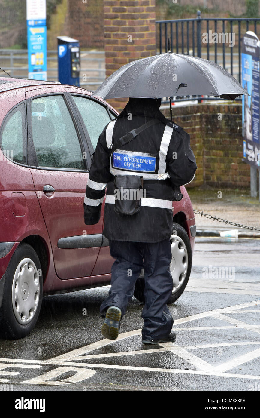 A traffic warden or civil enforcement office in a rain storm or checking vehicles and cars for tickets in the pouring Stock Photo