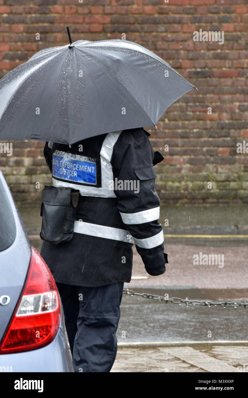 A traffic warden or civil enforcement office in a rain storm or checking vehicles and cars for tickets in the pouring - Stock Image
